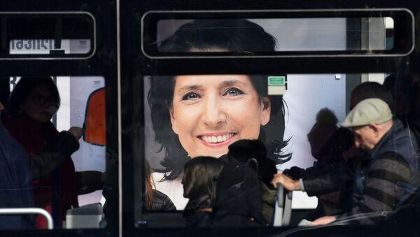 Люди на фоне предвыборного баннера Саломе Зурабишвили - Sputnik Грузия