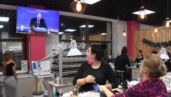 Женщины смотрят прямую трансляцию ежегодной большой пресс-конференции президента РФ Владимира Путина в салоне красоты во Владивостоке - Sputnik Грузия