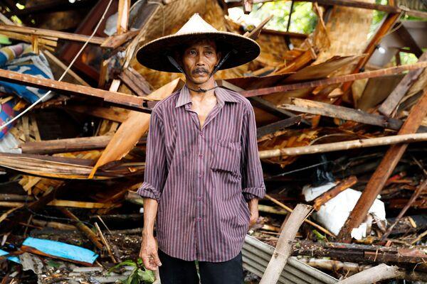Мужчина напротив разрушенного вследствие цунами дома в Индонезии - Sputnik Грузия