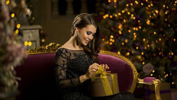 Девушка рапаковывает новогодний подарок - Sputnik Грузия