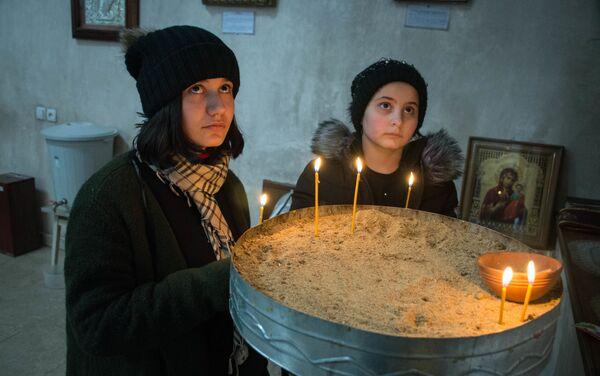 Первым делом девочки зашли в храм, чтобы поставить свечи за своих погибших родителей - Sputnik Грузия