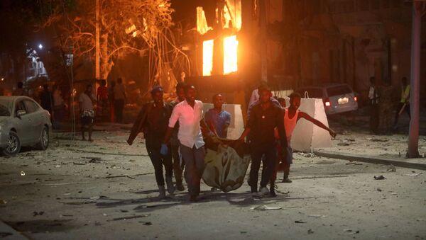 Спасатели эвакуируют раненого с места взрыва на улице Мака Аль Мукарам в Могадишо - Sputnik Грузия