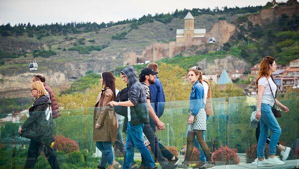 Люди гуляют по мосту мира в центре Тбилиси - Sputnik Грузия