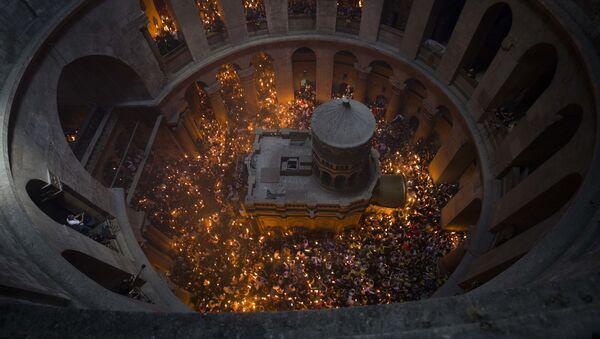 Верующие держат заженные от Благодатного огня свечи в храме Гроба Господня в Иерусалиме. Архивное фото - Sputnik Грузия