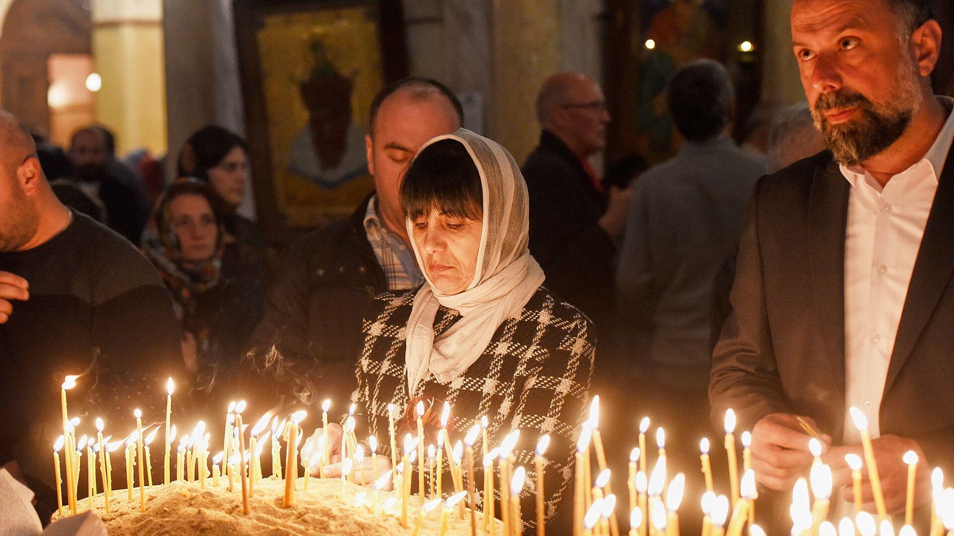 Верующие зажигают свечи во время Пасхального богослужения в храме Святой Троицы - Sputnik Грузия, 1920, 02.10.2021