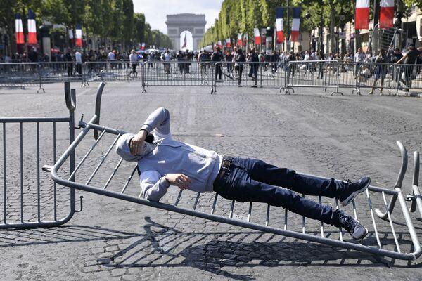 Молодой человек лежит  на ограждении во время беспорядков на Елисейских полях в Париже - Sputnik Грузия