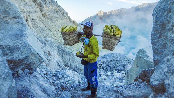 Шахтер переносит мешки с твердой серой из карьера на действующем вулкане Кава Иджен в Индонезии - Sputnik Грузия