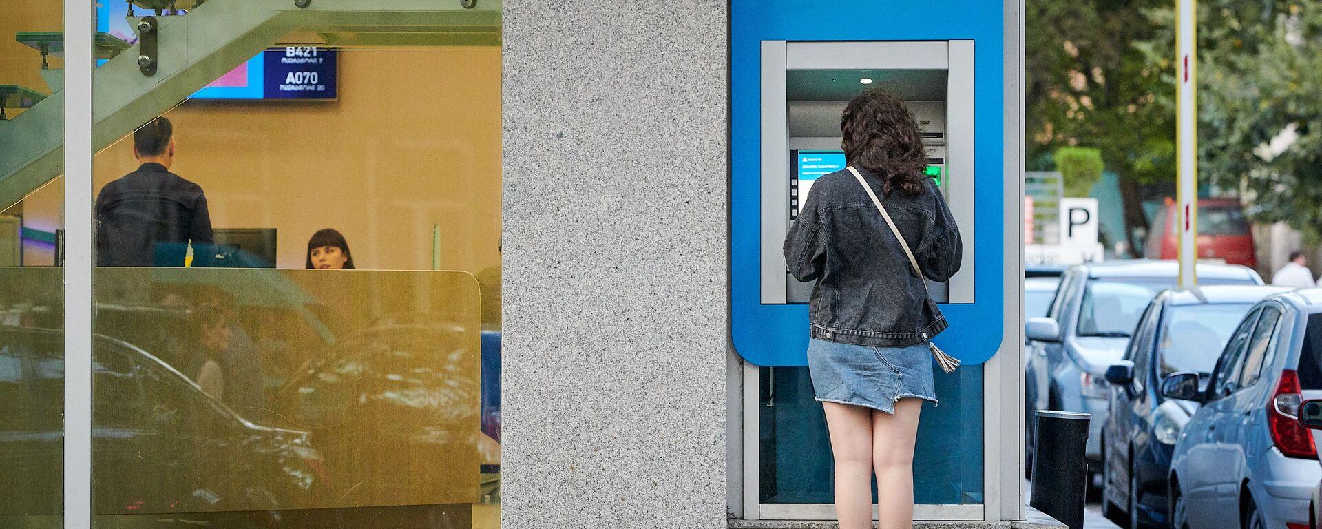 Девушка снимает деньги с карты в банкомате TBC bank - Sputnik Грузия, 1920, 18.03.2021