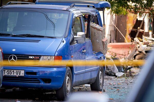 Каким-то машинам повезло больше - в этот микроавтобус, перелетев через всю улицу, на огромной скорости врезалась часть стены после взрыва. Но похоже, машину удастся восстановить - Sputnik Грузия