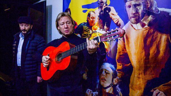 Известный российский актер театра и кино Дмитрий Харатьян играет на гитаре в коридоре Грибоедовского театра - Sputnik Грузия