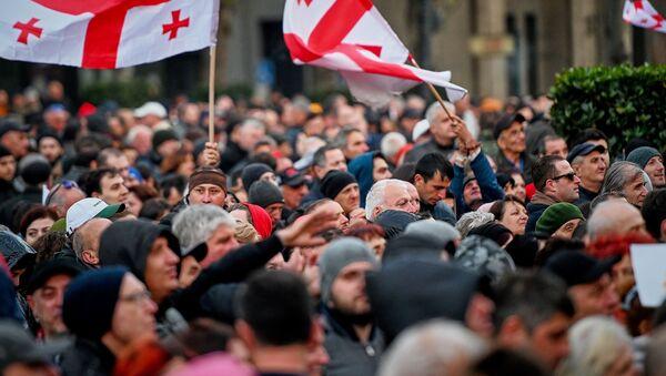 Оппозиция проводит акцию протеста. Люди держат в руках флаги Грузии. Митинг у парламента - Sputnik Грузия