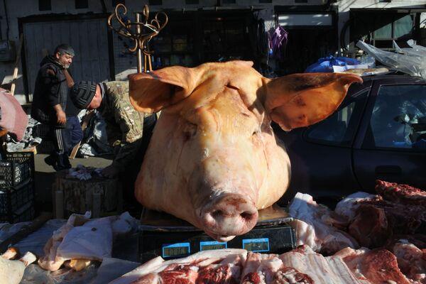 А тут целая свиная голова! Да, их тоже готовят на праздничное застолье и они также находят своего покупателя. На тбилисских рынках их можно встретить в мясных рядах - Sputnik Грузия