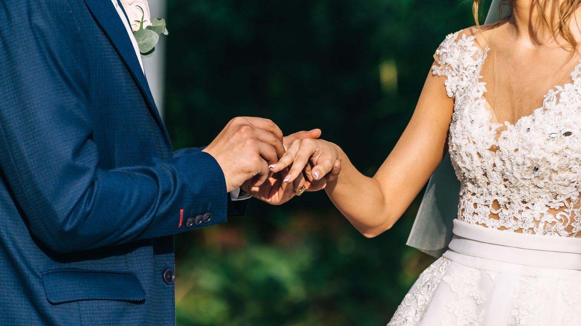 Жених и невеста во время свадебной церемонии. Невесте одевают на палец обручальное кольцо - Sputnik Грузия, 1920, 02.10.2021