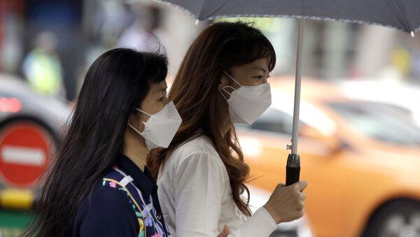 Девушки в масках от гриппа идут по улице - Sputnik Грузия