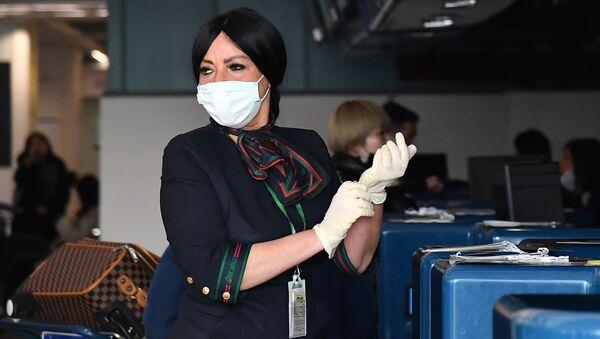 Сотрудница аэропорта в маске и перчатках до проверки пассажиров в Риме  - Sputnik Грузия