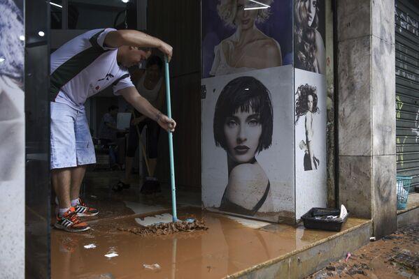 Мужчина убирает грязь с территории магазина, оставшуюся после наводнения в бразильском Белу-Оризонти - Sputnik Грузия