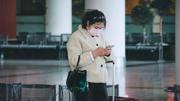 Турист с Востока в маске в тбилисском аэропорту читает сообщения в соцсети на смартфоне - Sputnik Грузия
