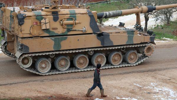 Ребенок проходит мимо турецкого 155-мм самоходного артиллерийского орудия в городе Бинниш в северо-западной провинции Сирии Идлиб - Sputnik Грузия