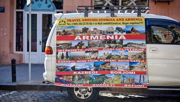 Предлагаются туры в Грузию и Армению. Баннер размещен на минивэне, припаркованном в центре грузинской столицы - Sputnik Грузия