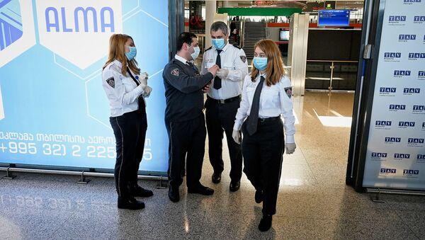 Сотрудники тбилисского аэропорта в защитных медицинских масках в зале прилета. Власти Грузии принимают меры против коронавируса - Sputnik Грузия