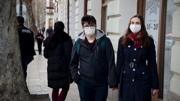 Влюбленная пара идет по улице в масках защищая себя от коронавируса - Sputnik Грузия
