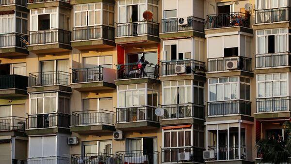 Женщина упражняется на своем балконе во время карантина в рамках 15-дневного чрезвычайного положения для борьбы с коронавирусом COVID-19 в центре города Торремолинос, на побережье Коста-дель-Соль, на юге Испании - Sputnik Грузия