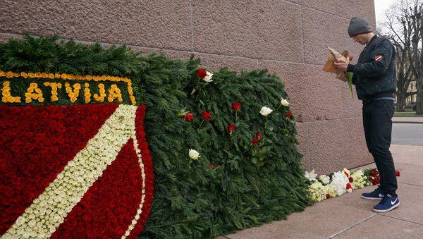 Сторонник латышского легиона Ваффен СС возлагает цветы к памятнику Свободы в Риге - Sputnik Грузия