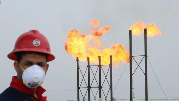 Мужчина в защитной маске на фоне факельных труб на нефтяном месторождении Нар Бин Умар - Sputnik Грузия