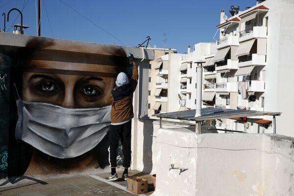 В Афинах 16-летний автор S.F. изобразил на крыше многоквартирного дома женщину в медицинской маске - своеобразный призыв беречь себя - Sputnik Грузия
