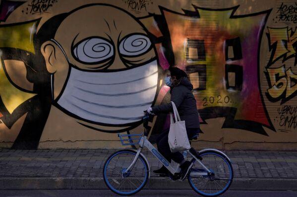 Граффити на строительной площадке в Шанхае, мимо которого проезжает женщина в защитной маске на велосипеде - Sputnik Грузия