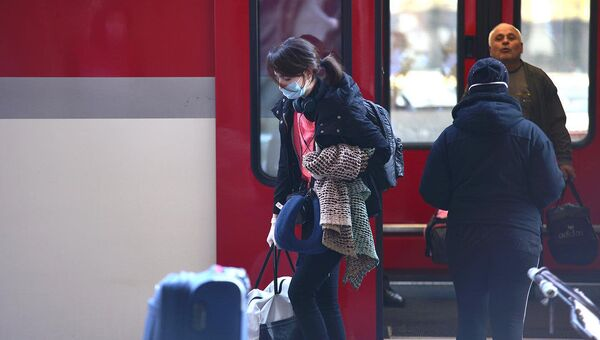 Девушка в маске выходит из пассажирского поезда Stadler. В Грузии пытаются остановить распространение коронавируса - Sputnik Грузия