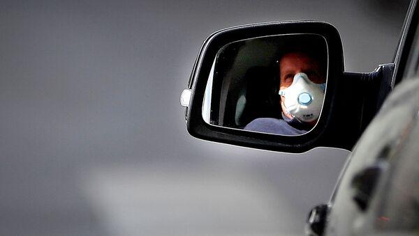 Водитель в респираторе едет за рулем своей машины по улицам Рима в Италии - Sputnik Грузия