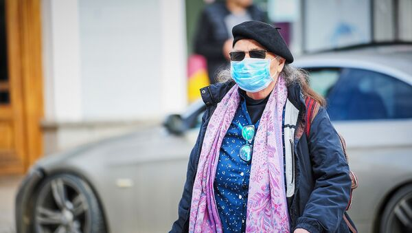 Пожилая женщина в маске идет по улице в центре города. В Грузии борются с коронавирусом - Sputnik Грузия