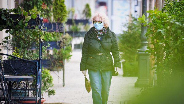 Пожилая женщина идет по улице в медицинской маске. В Грузии борются с коронавирусом - Sputnik Грузия