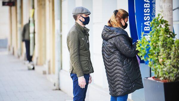 Мужчина в кепке и синей маске и женщина в перчатках и черной маске на улице у банкомата. В Грузии борются с коронавирусом - Sputnik Грузия