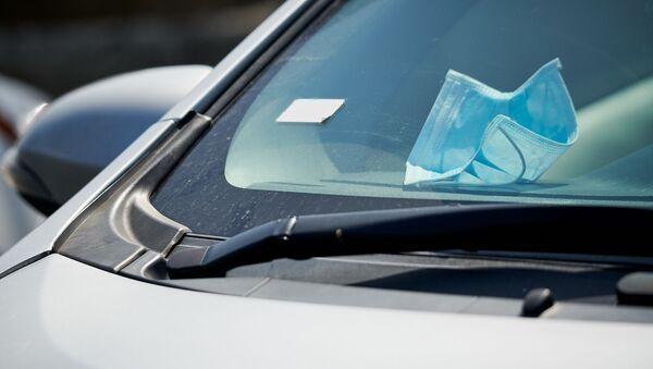 Защитная медицинская маска лежит на торпедо в салоне автомобиля. В Грузии введен карантин и принимаются меры по борьбе с коронавирусом - Sputnik Грузия