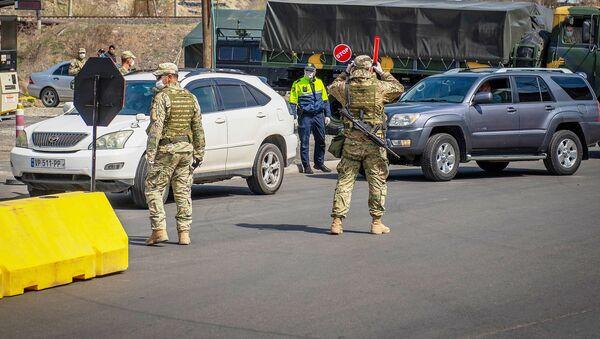 Полицейские и военные на блокпосту на въезде в Тбилиси со стороны Рустави. В Грузии введен карантин и комендантский час из-за коронавируса - Sputnik Грузия