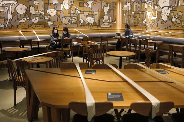 Обозначенные лентой столы для соблюдения социальной дистанции в кафе в Гонконге  - Sputnik Грузия