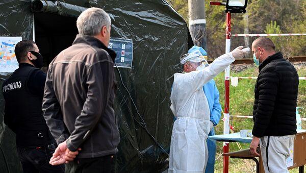 Медики измеряют температуру жителям в полевом госпитале на блокпосту на дороге между столицей Грузии и Мцхета - Sputnik Грузия