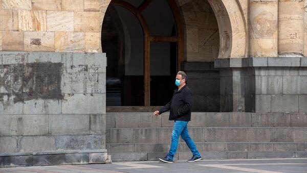 Прохожий в защитной маске на площади Республики (26 марта 2020). Ереван - Sputnik Грузия