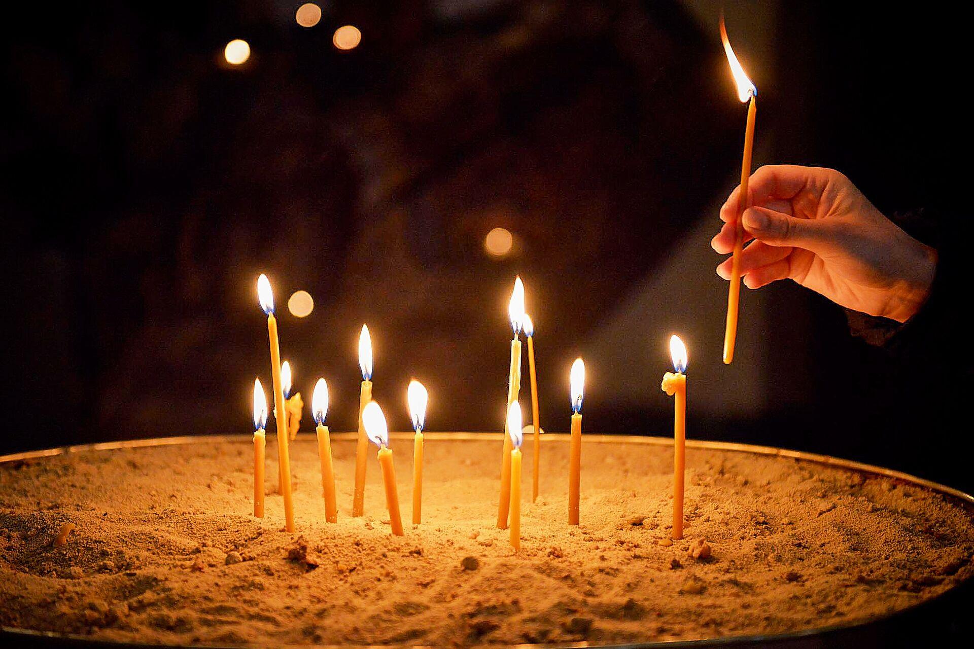 Верующие ставят свечи в храме. Кафедральный собор Святой Троицы Самеба во время карантина - Sputnik Грузия, 1920, 12.10.2021