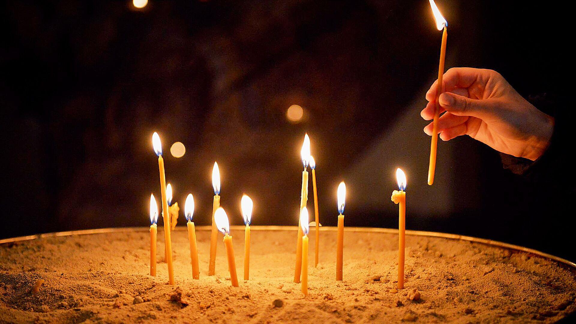 Верующие ставят свечи в храме. Кафедральный собор Святой Троицы Самеба во время карантина - Sputnik Грузия, 1920, 07.10.2021
