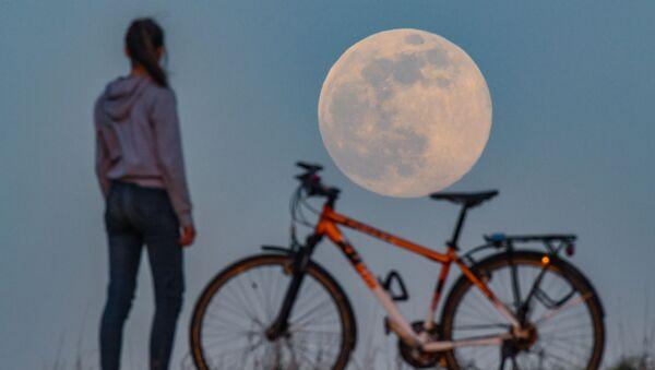 Девушка с велосипедом наблюдает за суперлунием в Зиверсдорфе, Германия - Sputnik Грузия