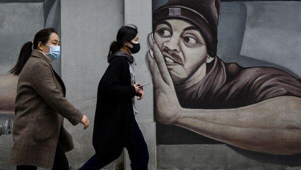 Девушки в масках напротив граффити в Ухане  - Sputnik Грузия