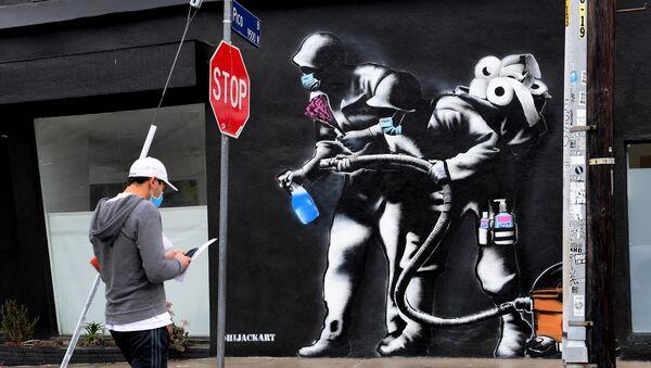 Прохожий напротив граффити, посвященного борьбе с коронавирусом, в Лос-Анджелесе - Sputnik Грузия