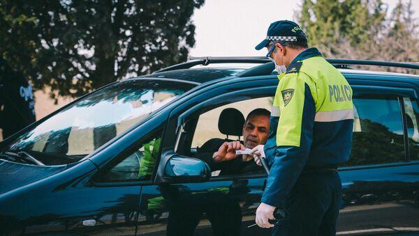 Сотрудник патрульной полиции проверяет документы у водителей на блокпосту в Марнеули - Sputnik Грузия