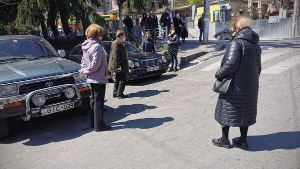 Похороны Гоги Цагарели. Несколько человек стояли на улице, на расстоянии друг от друга. Так известного фотографа проводили в последний путь - Sputnik Грузия