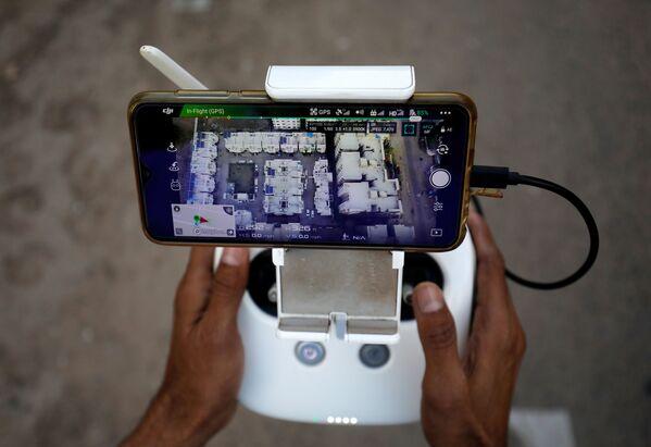 Пульт управления беспилотником для наблюдения за передвижением людей в связи с коронавирусом в жилом районе в Ахмедабаде в Индии - Sputnik Грузия