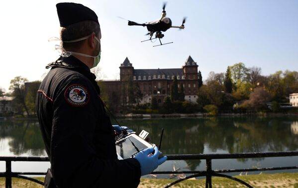 Итальянский карабинер управляет беспилотником в целях проверки выполнения населением мер, введенных правительством в связи с коронавирусом в Турине - Sputnik Грузия