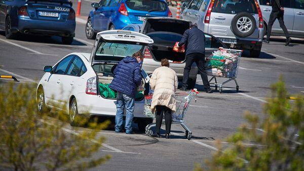 Люди с покупками у одного из столичных гипермаркетов. Жители запасаются продуктами перед Пасхой - Sputnik Грузия